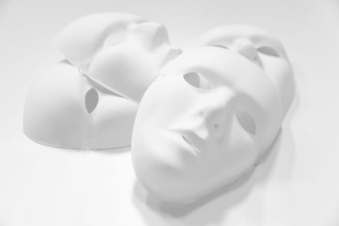 Four white plastic mask are arranged in a dramatic high key conceptual photograph representing brand duplicity