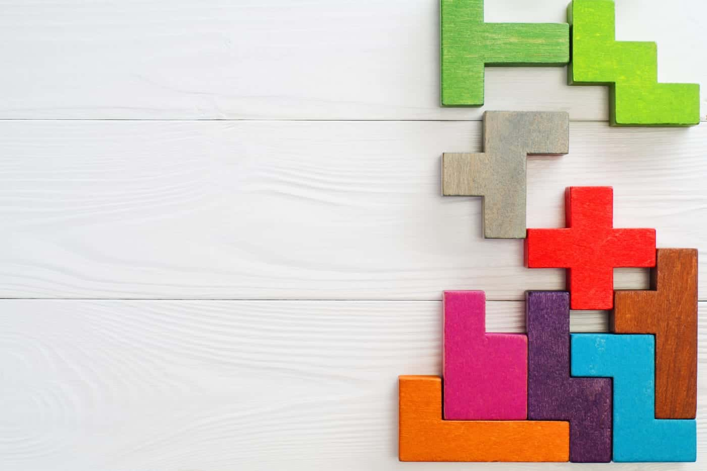Concept of alignment between brand and culture with different colourful wooden blocks on white wooden background different shapes fitting together