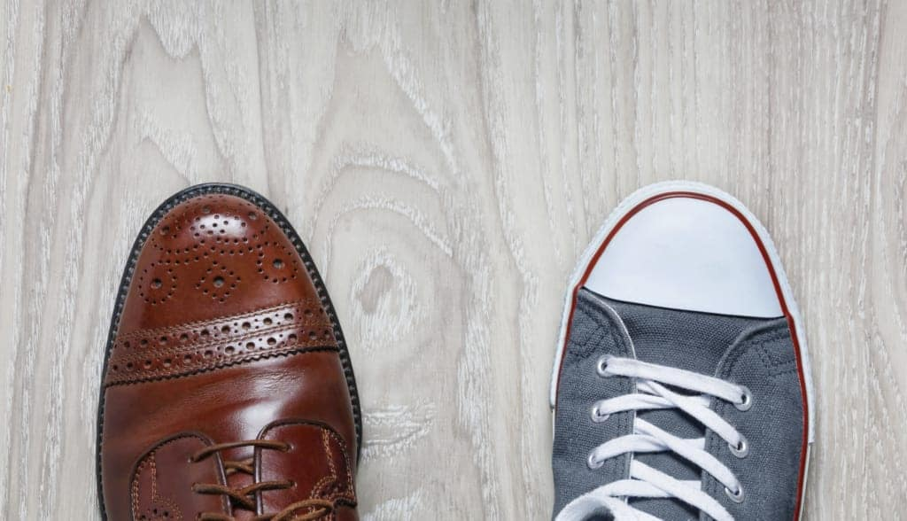two mismatched shoes one leather business shoe and one sneaker on a pale wooden floor representing mismatched brand and culture