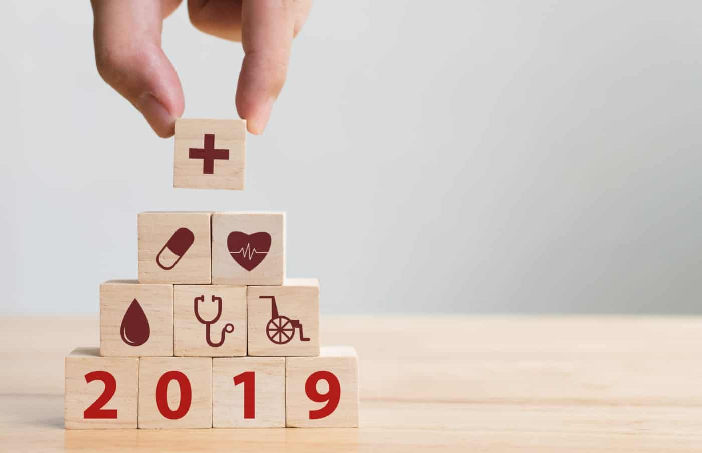 Hand arranging wood block stacking with healthcare medical icons representing the South African Company Culture Health Index 2019