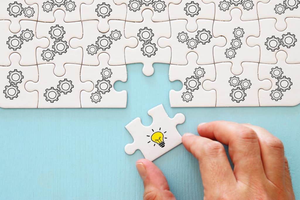 Concept image of revealing an idea, finding the right solution during creative process. Hand picking piece of puzzle with bright light bulb representing Low-cost employee engagement ideas