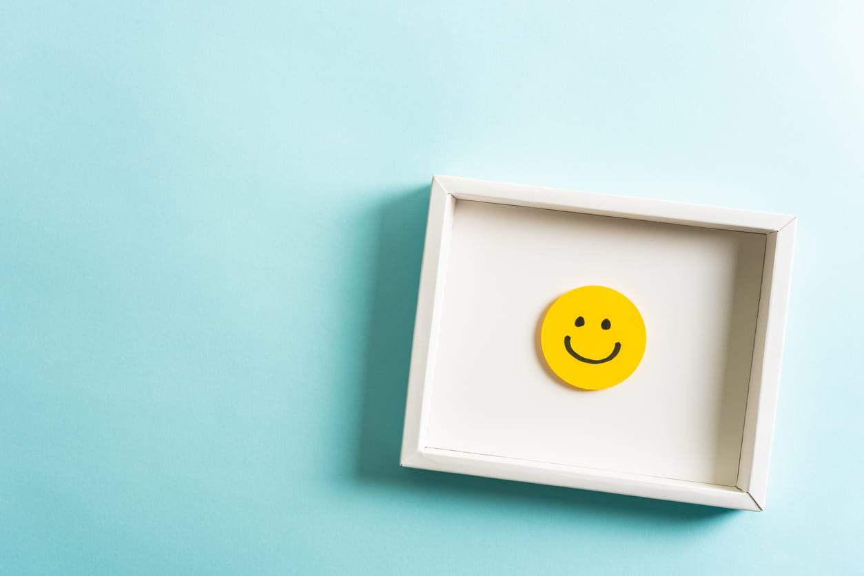 Employee engagement represented by Concept of well-being, well done, feedback, employee recognition award. Happy yellow smiling emoticon face frame hanging on blue background with empty space for text.