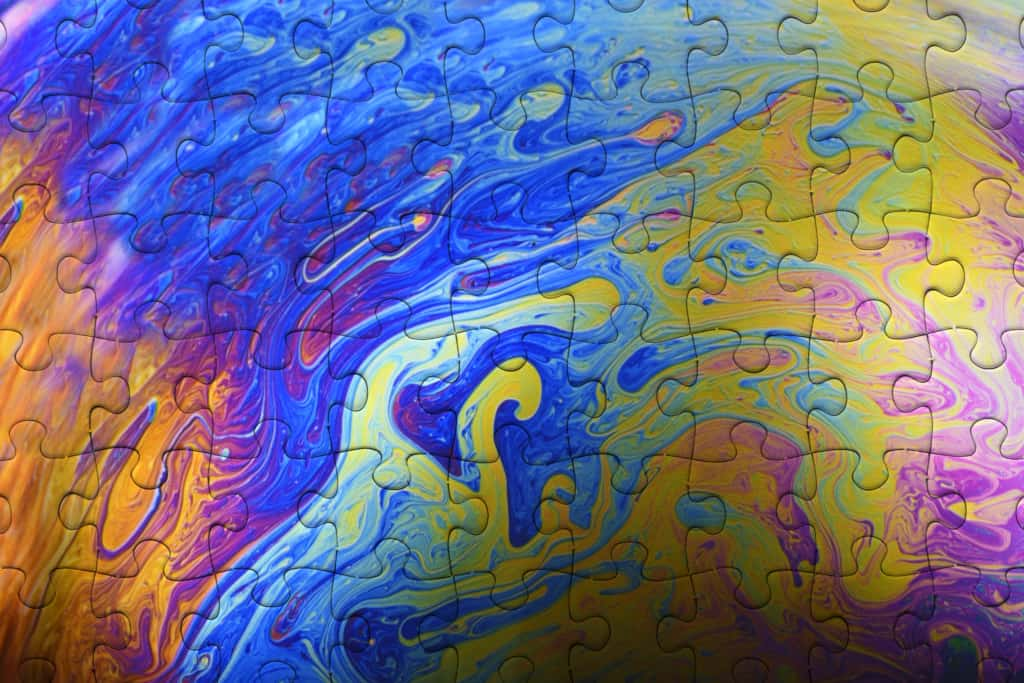 Creativity at work represented by overhead shot of Jigsaw Puzzle from made with rainbow colored soap bubble.