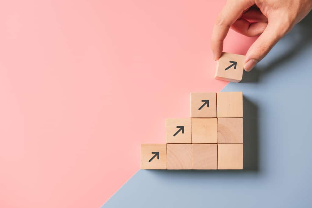 Business concept marketing in a crisis leads to growth success process, Close up woman hand arranging wood block stacking as step stair on paper blue and pink background, copy space.